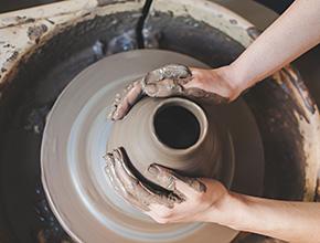 Hands shaping a pot